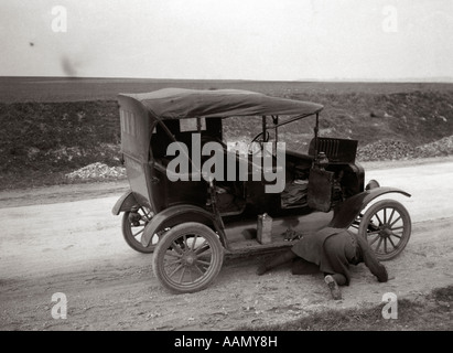 1920s 1930s MAN ON HIS HANDS AND KNEES LOOKING UNDER MODEL T BROKEN DOWN ON ROADSIDE - Stock Photo