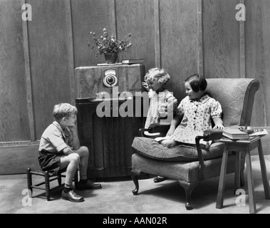 1930s TWO LITTLE GIRLS AND A BOY SITTING IN LIVING ROOM LISTENING TO RADIO - Stock Photo