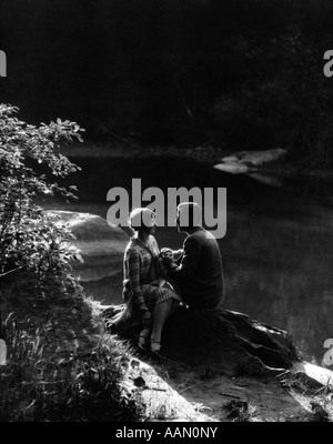 1920s 1930s ROMANTIC COUPLE SITTING BY STREAM IN SOFT MOODY AFTERNOON SUNLIGHT - Stock Photo