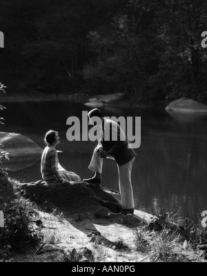 1920s 1930s WOMAN SITTING ON ROCK LAKESIDE TALKING TO MAN STANDING WITH FOOT ON ROCK LEANING ON KNEE LISTENING - Stock Photo