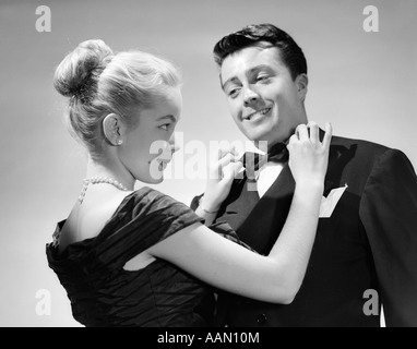 1950s COUPLE IN FORMAL ATTIRE WOMAN WITH BLOND HAIR PULLED BACK IN BUN ADJUSTING MAN'S BOW TIE SMILING PERKY CUTE - Stock Photo