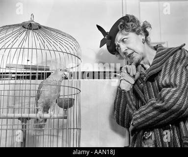 1940s FUNNY WOMAN IN HAT & COAT TALKING TO PARROT IN BIRD CAGE - Stock Photo