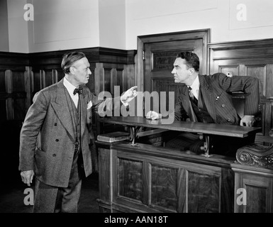 1940s 1950s 2 MEN ATTORNEY LAWYER POINT ARGUE CASE BEFORE JUDGE LAW COURTROOM BENCH LEGAL - Stock Photo