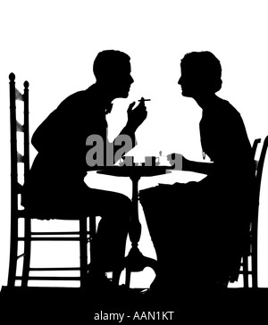 1920s COUPLE AT TABLE WITH TEACUPS MAN SMOKING CIGARETTE - Stock Photo
