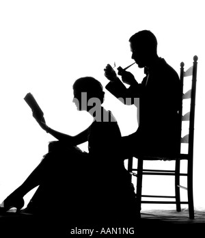 1920s 1930s ANONYMOUS SILHOUETTED MAN IN LADDER-BACK CHAIR SMOKING PIPE WITH WOMAN SEATED ON FLOOR IN FRONT OF HIM - Stock Photo