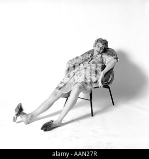 1970s WOMAN SLOUCHED IN CHAIR WITH EXHAUSTED EXPRESSION WEARING NIGHTGOWN HOUSECOAT SLIPPERS - Stock Photo