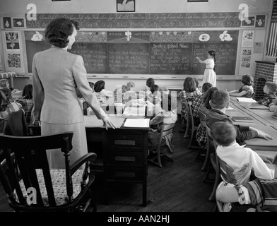 1950s GIRL AT FRONT OF CLASSROOM USING POINTER TO READ THROUGH SCHOOL NEWS ON CHALKBOARD WITH TEACHER STANDING AT - Stock Photo