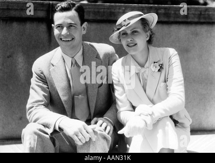 1930s SMILING COUPLE SITTING OUTDOORS IN THE SUNLIGHT - Stock Photo