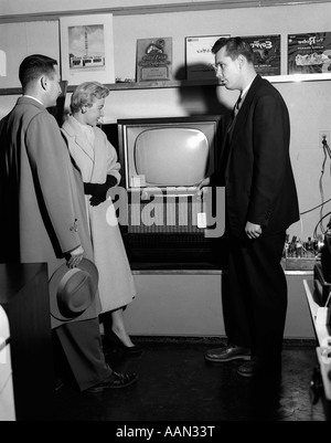 1950s COUPLE WITH SALESMAN IN ELECTRIC APPLIANCE STORE SHOPPING FOR TELEVISION - Stock Photo