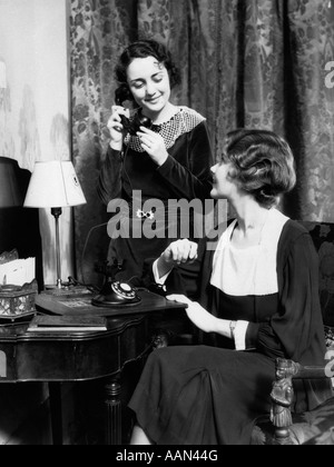 1930s TWO SMILING WELL DRESSED WOMEN ONE SITTING ONE STANDING BY VANITY TABLE TALKING ON TELEPHONE - Stock Photo