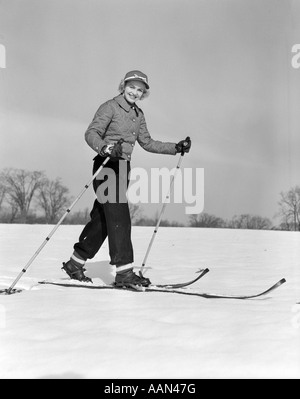 1940s 1950s WOMAN SMILING LOOKING AT CAMERA ON WOOD SKIS WITH BAMBOO SKI POLE IN EACH HAND WEARING QUILTED JACKET - Stock Photo
