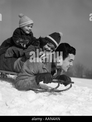 1930s FATHER DAUGHTER AND SON PILED ON SLED GOING DOWNHILL IN SNOW LAUGHING - Stock Photo