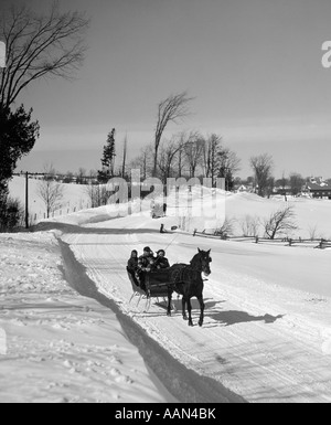 1960s FAMILY DRIVING DOWN RURAL ROAD IN ONE HORSE OPEN SLEIGH - Stock Photo