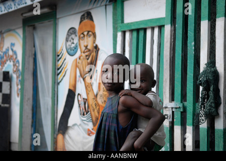 Young Congolese girl carries her brother on her back in the city of Goma North Kivu province in the eastern Democratic - Stock Photo