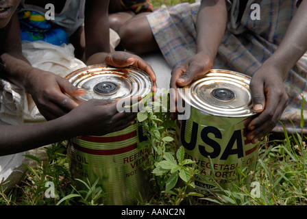 Internally displaced children holding cans of refined vegetable oil donated by USAID at World Food Programme WFP - Stock Photo