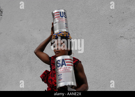 Internally displaced woman carrying box of refined vegetable oil donated by USAID at World Food Programme WFP distribution - Stock Photo