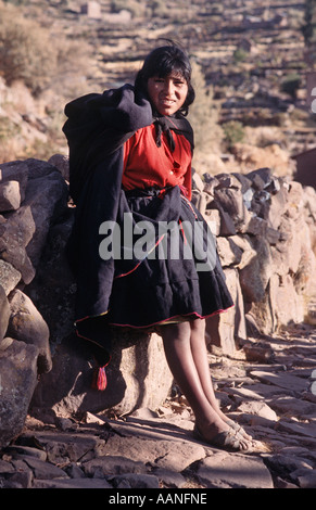 Young woman from Taquile in local style tribal dress Taquile island Lake Titicaca Peru - Stock Photo