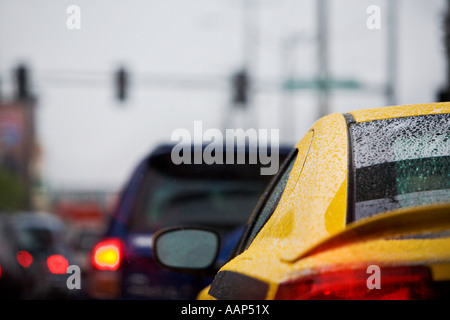 Water beads up on the body and window of a yellow car in traffic on a rainy day in Seattle WA - Stock Photo