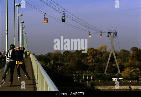 Roller skating on the Zoo Bridge across the river Rhine in Cologne, North Rhine Westphalia, Germany - Stock Photo