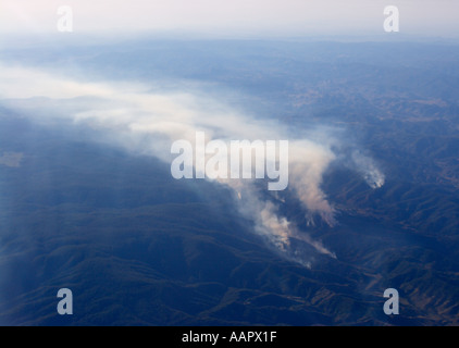 Aerial view of bush fire burning on several fronts giving out a huge cloud of drifting smoke in New South Wales Australia