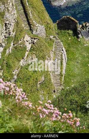 dh  WHALIGOE CAITHNESS Man walking down steep stone steps to cove harbour seacliff scotland coast