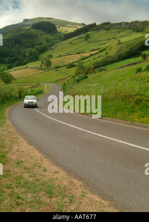 A road near the town of Lages through hilly patchwork farm fields on the island of Flores in the Azores - Stock Photo