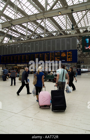 dh  CENTRAL STATION GLASGOW Passenger couple with suitcases looking at train timetable board - Stock Photo
