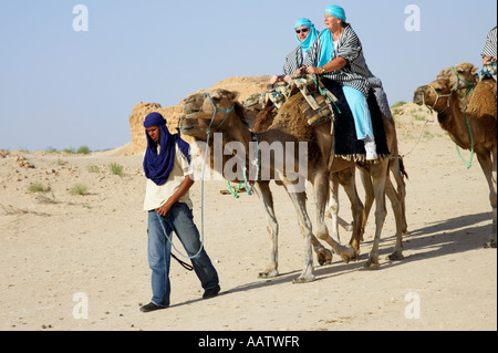 mrazig guide in modern clothing leads british tourists riding camels and wearing desert clothes into the sahara - Stock Photo