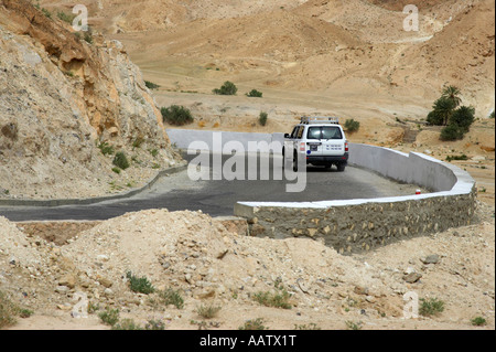 off road tourist 4x4 vehicle driving down steep winding mountain road in the mountains tunisia - Stock Photo