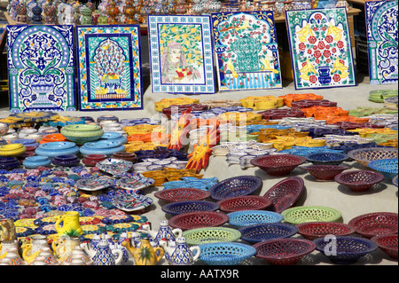 rows of local speciality ceramics for sale to tourists on a stall in the souk market in nabeul tunisia - Stock Photo