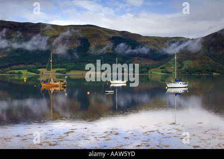 Three sailing boats on Loch Loch Leven near Ballachulish Glencoe with light clouds drifting by the mountainous backdrop - Stock Photo