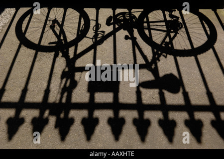 Shadow of a bike leaning against wrought iron railings Dublin Republic of Ireland Europe - Stock Photo