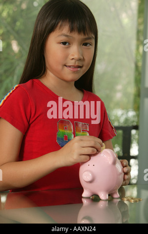 Girl wearing red shirt posing with her piggy Bank - Stock Photo