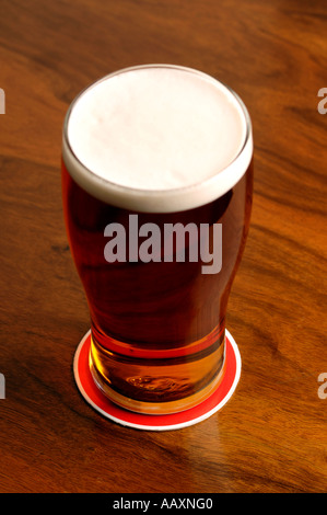 Full pint of beer on a beer mat on a wooden pub table - Stock Photo