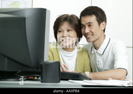 Couple in font of Computer - Stock Photo