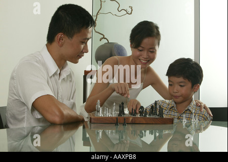 Family of three playing chess - Stock Photo