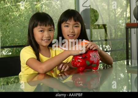 Siblings with Piggy bank - Stock Photo