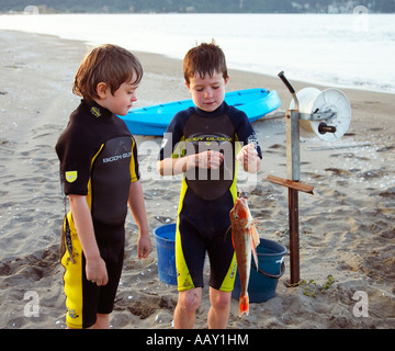 two proud boys having caught a gurnard whilst long lining in summer - Stock Photo