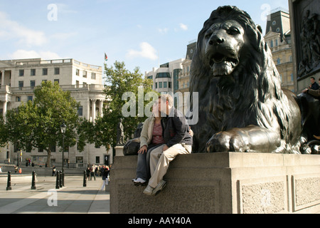 Young couple by one of the lions in Trafalgar Square London England - Stock Photo