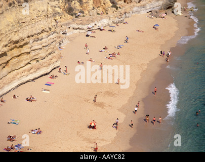 Aerial view from above looking down on people playing & sunbathing on sandy family holiday seaside beach near Carvoeiro - Stock Photo