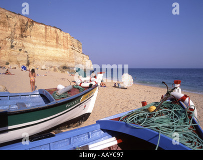 Algarve Benagil holiday beach with fishing boats and people sunbathing cliffs beyond Portugal Europe - Stock Photo