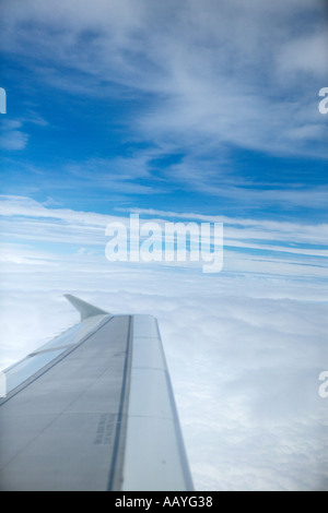 Airplanes wing in blue sky with white clouds aerial from aeroplane aircraft - Stock Photo