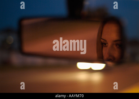 Rear View Mirror with Reflection of a Womans Face in a Car Driving Along a Road at Night - Stock Photo