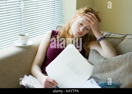 A young woman feeling stressed out with paperwork / mortgage / debts / bills - Stock Photo