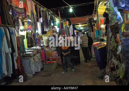 Customers and stall keepers in covered market stalls at night in old town Ed Dahar region Hurghada Red Sea Egypt - Stock Photo
