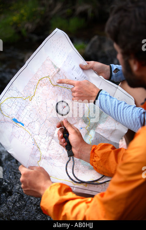 Hikers looking at map and compass - Stock Photo