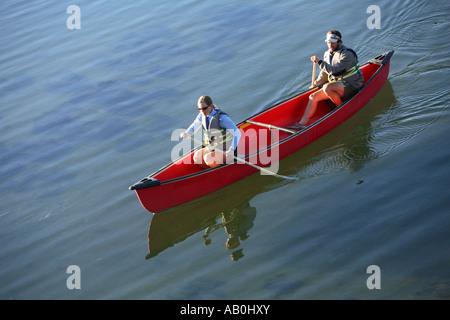 Couple paddle canoe on lake - Stock Photo