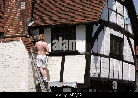 Workman with ladder on the exterior of an old tudor cottage in summer at Shere Surrey England UK - Stock Photo
