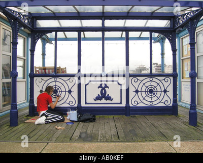 young woman repainting pier ornaments in Eastbourne England United Kingdom - Stock Photo