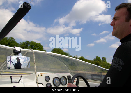 early 30s dark haired man driving speedboat during waterski session with blue cloudy sky looking front - Stock Photo